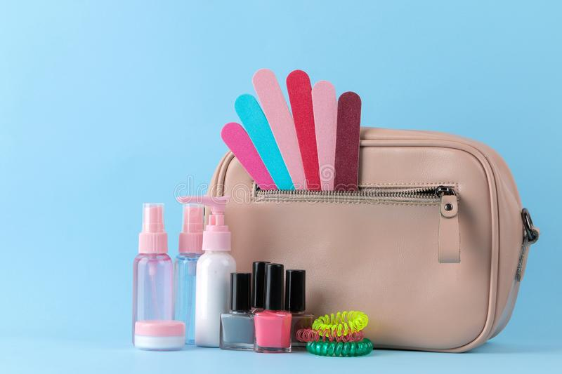 Stylish fashionable pink bag and women`s cosmetics and accessories on a bright trendy naked background. female accessory concept royalty free stock image