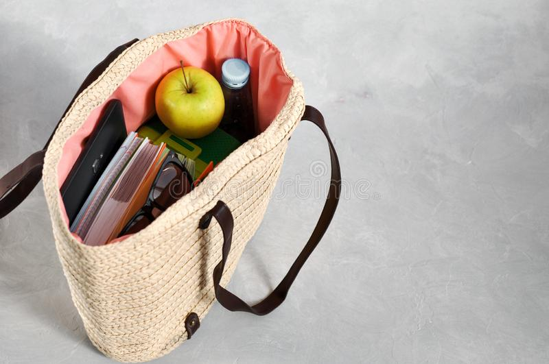 Stylish fashionable wicker bag with textbooks and notebooks, lunchbox and green Apple, water for a snack and sunglasses stock photography