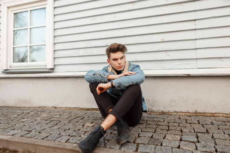 Stylish fashionable young guy in a denim fashion jacket. With black pants and shoes sitting near a wooden house royalty free stock photo