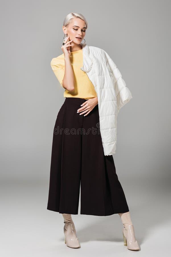 Stylish female model posing with jacket over shoulder. Isolated on grey background stock photo