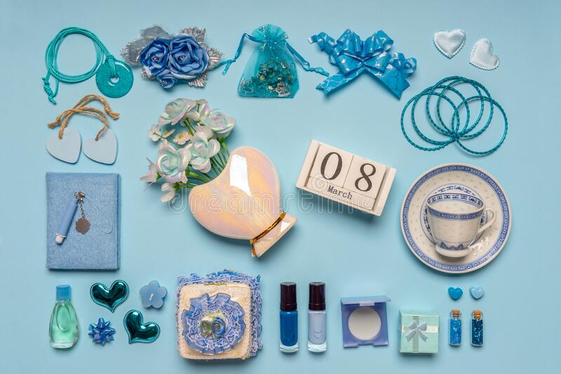 Stylish feminine accessories in blue colors on blue pastel background. Calendar date 8 March, bouquet of flowers in vase,. Cosmetics, jewellery, hearts, bows stock images