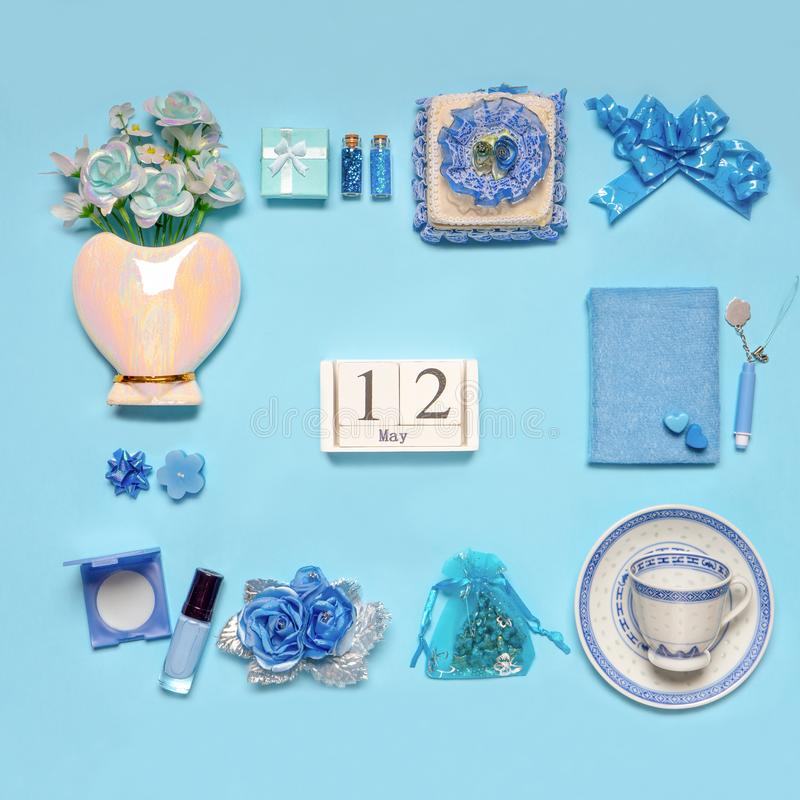 Stylish feminine accessories, flowers, cosmetics, gifts and decorative items in blue pastel colors on blue background. Calendar. Date May 12. Greeting card for royalty free stock photos