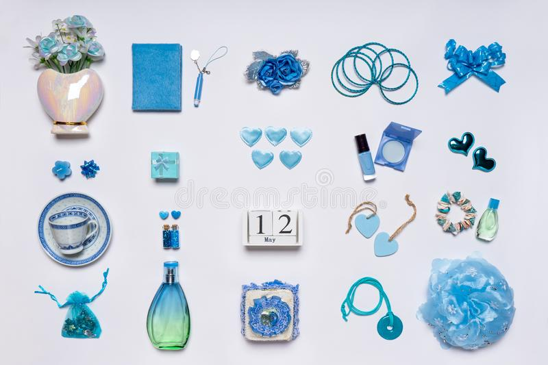 Stylish feminine accessories, flowers, cosmetics, jewelery, perfume in blue pastel colors on white background. Calendar date May. 12, greeting card for mother`s royalty free stock photos
