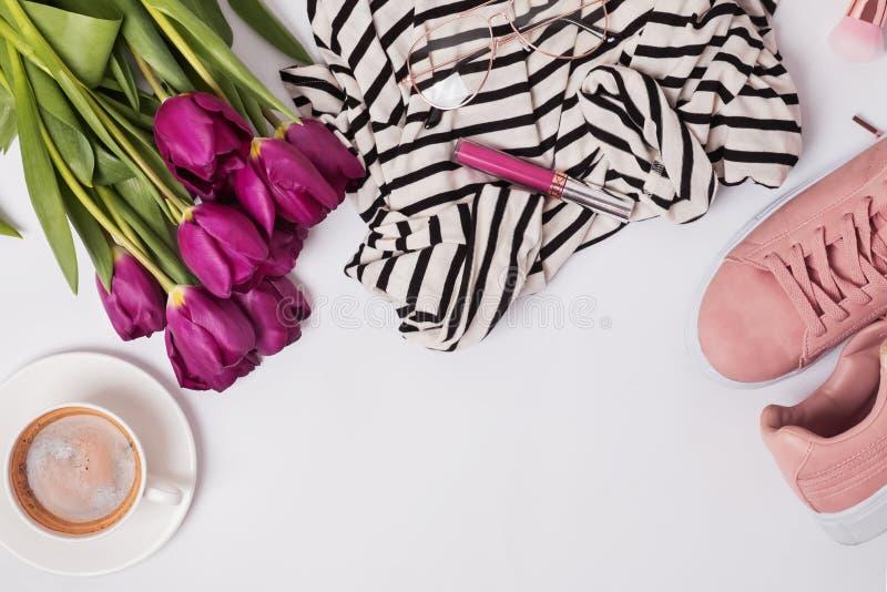 Stylish feminine essentials, coffeee and purple tulips. Spring flat lay royalty free stock image
