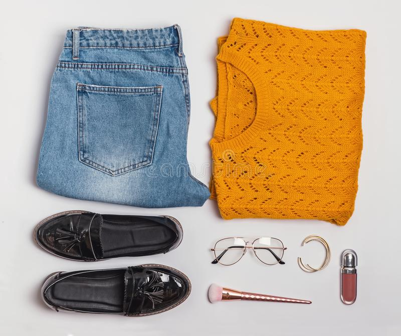 Stylish flat lay with feminine aitumn outfit sweater, jeans and shoes. Stylish flat lay with feminine aitumn outfit sweater, jeans, shoes and other accessories royalty free stock images