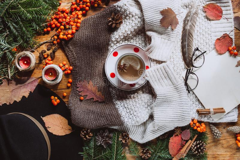 Stylish Flat lay view of autumn leaves and textured scarf on wooden background with cup . Autumn or Winter concept. stock images