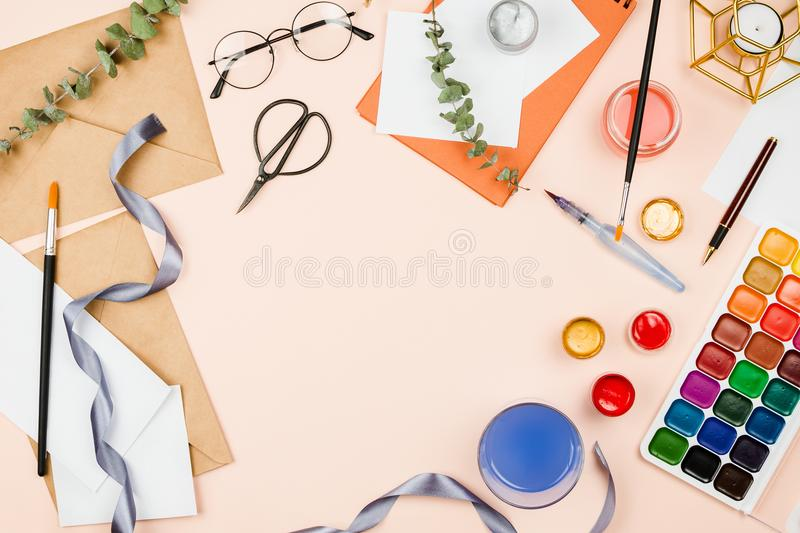 Stylish flatlay with art supplies, envelopes, brushes, watercolors, glasses, pen and other stationary and art supplies stock photo