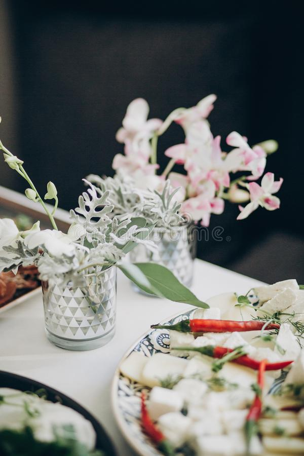 Stylish floral decor on wedding table. White eustoma and orchid flowers in glass and delicious appetizers on wedding centerpiece. stock photos