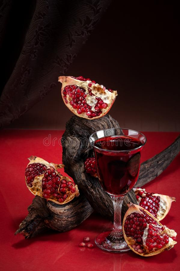Stylish food photography in the theater surroundings - ripe pomegranate and pomegranate juice. Shooting in a discreet style. Stylish food photography in the stock photos