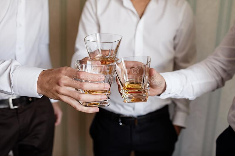 Stylish friends businessmen in suits toasting with glasses of whiskey indoors, closeup. groom`s morning stock images