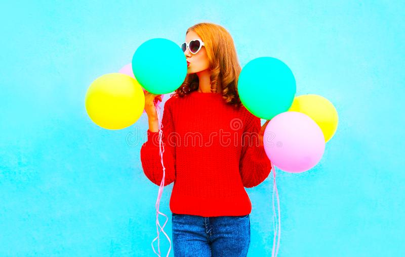 Stylish funny girl kisses an air colorful balloons on a blue royalty free stock photography
