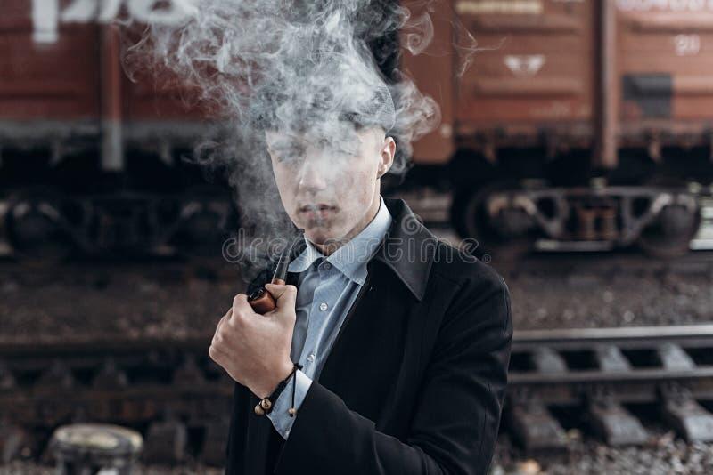 Stylish gangster man smoking. posing on background of railway. e stock photos