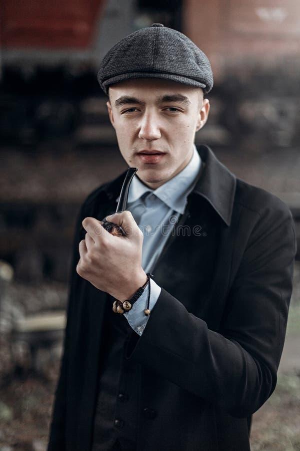Stylish gangster man smoking. posing on background of railway. e royalty free stock photography