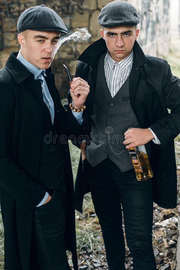 Stylish gangsters smoking in tweed outfit posing on background o royalty free stock images