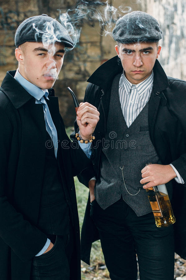 stylish gangsters smooking and holding whiskey in retro look posing on background of railway. england in 1920s theme. fashionable royalty free stock photos