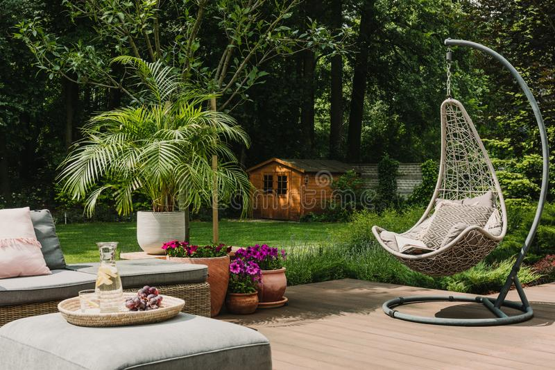 Stylish garden decoration with fancy egg chair and garden furniture. Stylish garden decoration with egg chair and garden furniture royalty free stock photography