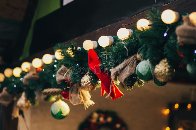 Stylish garland lights and fir branches with christmas decorations on wooden cabins at european city market. Festive street decor royalty free stock photography
