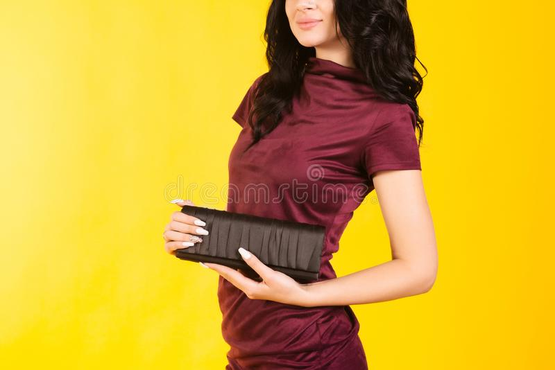 Stylish girl in a burgundy dress holding a purse on a yellow background stock photography