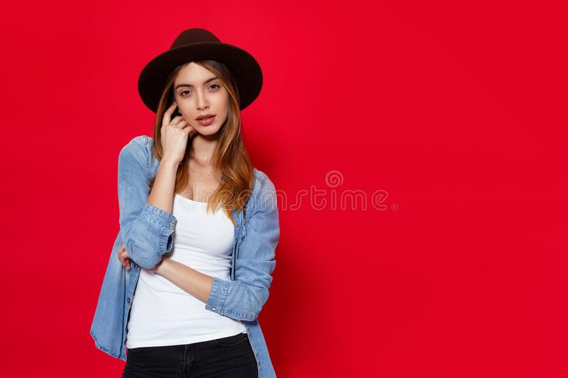 Fashion beauty portrait of attractive young woman in hat posing with attitude looking at camera, over red background. stock images