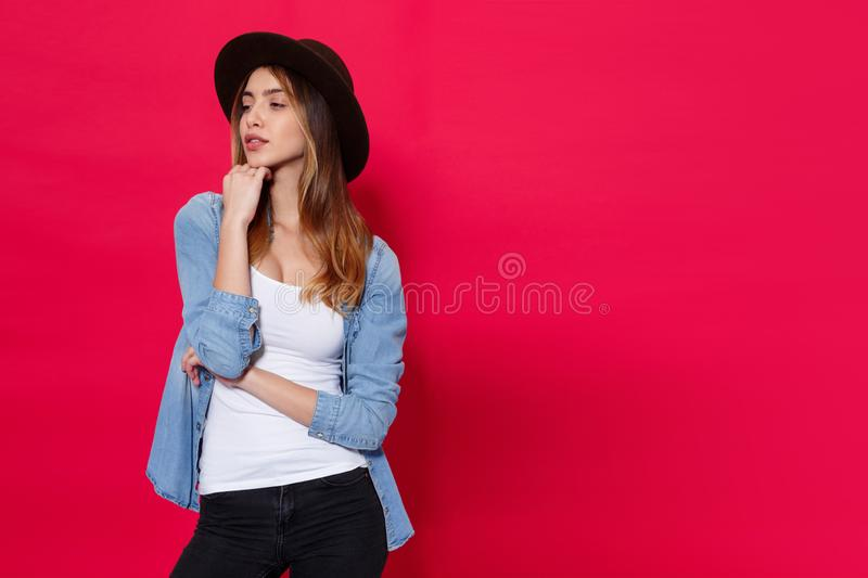 Stylish girl in casual clothes and brown hat, posing with attitudine in studio over light red background. royalty free stock photo