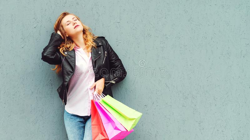 Stylish girl enjoying after great shopping. Shopper woman holding shopping bags. Girl posing against grey wall, copy space. stock images
