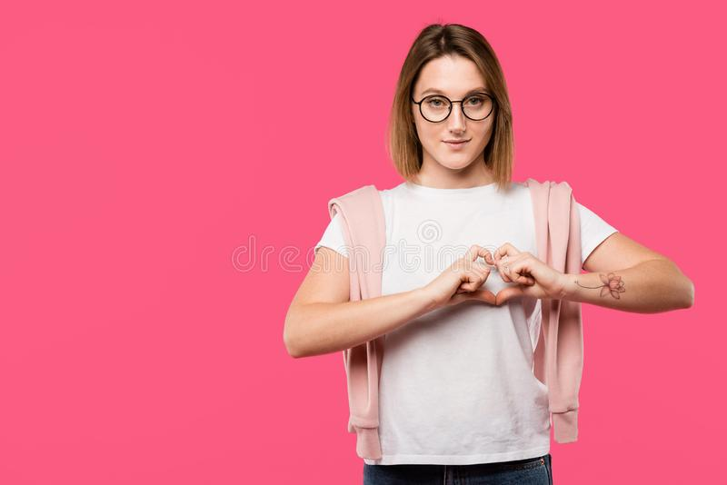 Stylish girl in eyeglasses showing heart symbol isolated. On pink royalty free stock images