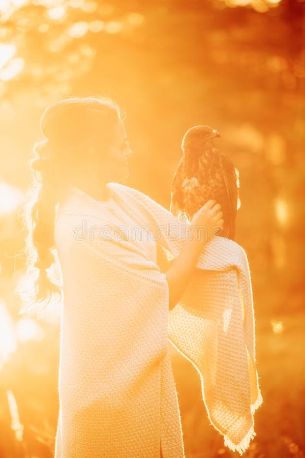 Stylish girl and a falcon in the autumn forest in the rays of the setting sun royalty free stock photo