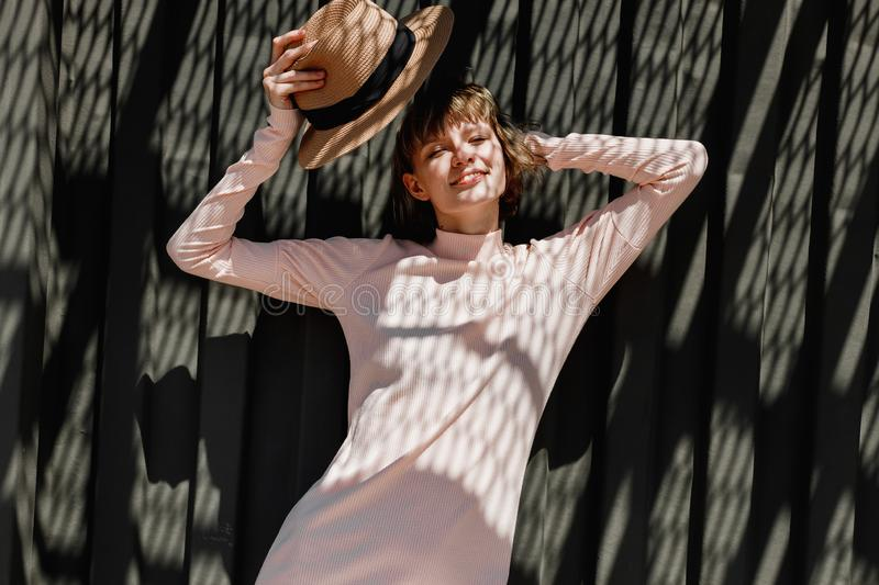 Stylish girl in a gently pink dress and straw hat standing next to a dark metal fence in the sunlight with reflected royalty free stock photos