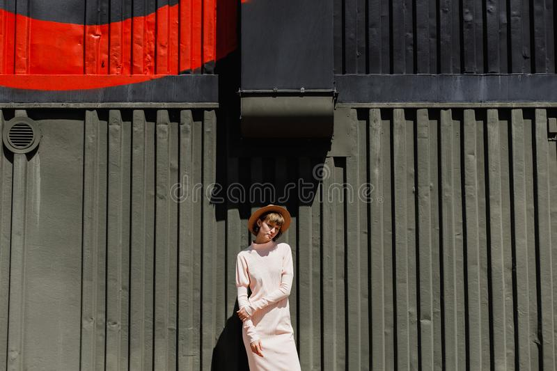 Stylish girl in a gently pink dress and straw hat standing next to a dark metal fence on a sunny day.  stock image