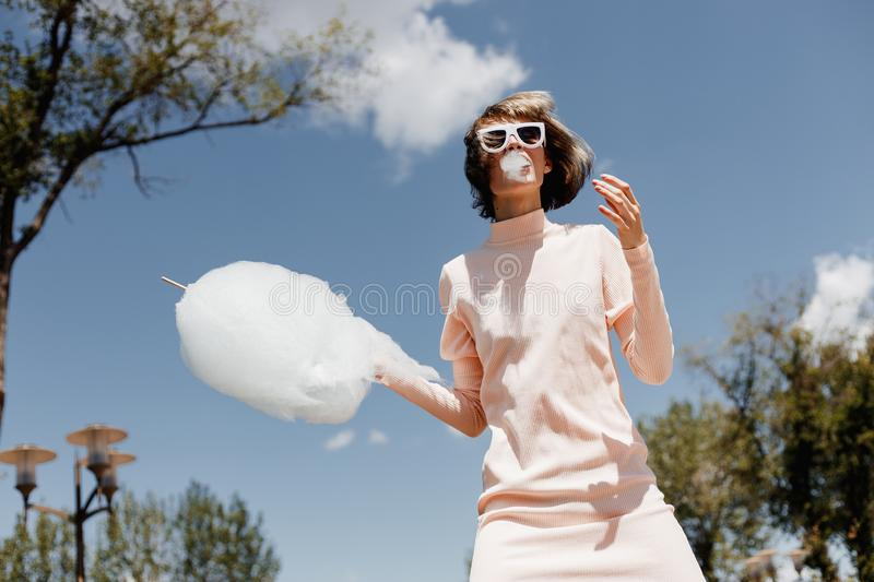 Stylish girl in a gently pink dress and pink visor eats a cotton candy in the street on a sunny day royalty free stock photo