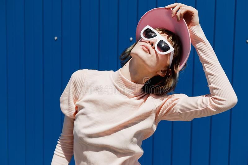 Stylish girl in a gently pink dress, white sunglasses and pink visor poses against a bright blue metal wall outside on a stock image
