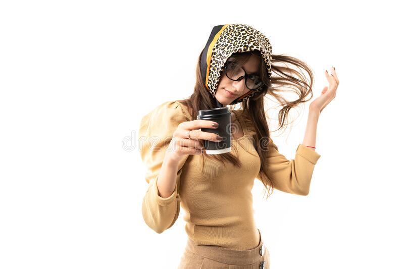 Stylish girl with a headdress, a scarf and fluttering hair holds a cup of coffee on a white background.  royalty free stock photography