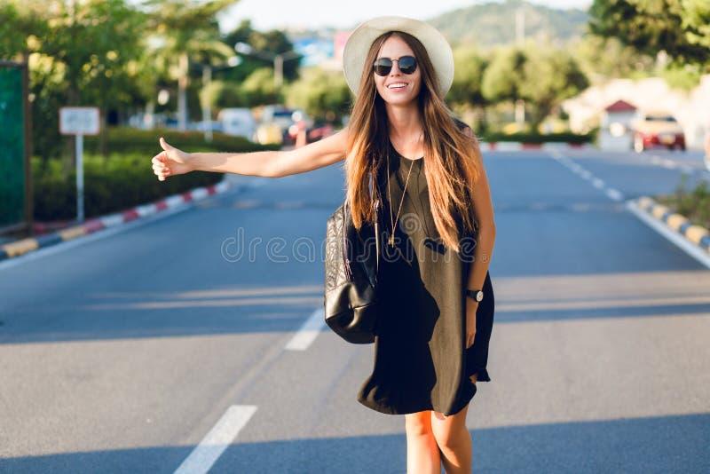 Stylish girl hitchhiking on the road wearing short black dress, straw hat, black eyeglasses, and black backpack. She stock images