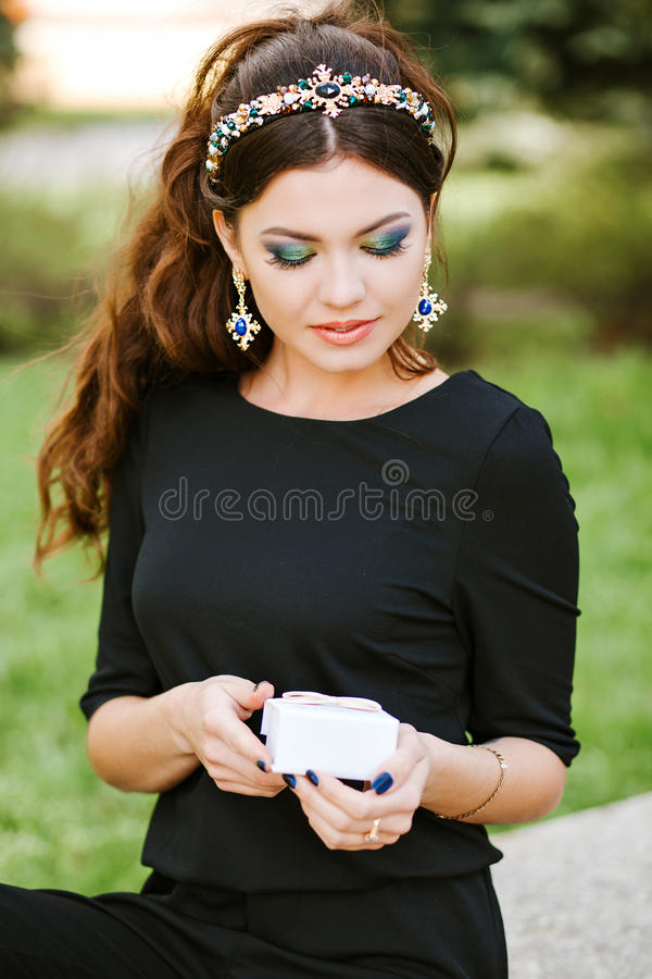 Stylish Girl Holding A Gift. Wearing A Black Dress, Expensive ...