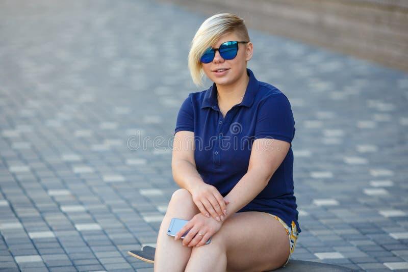 Stylish girl plus size sitting on a longboard stock photo