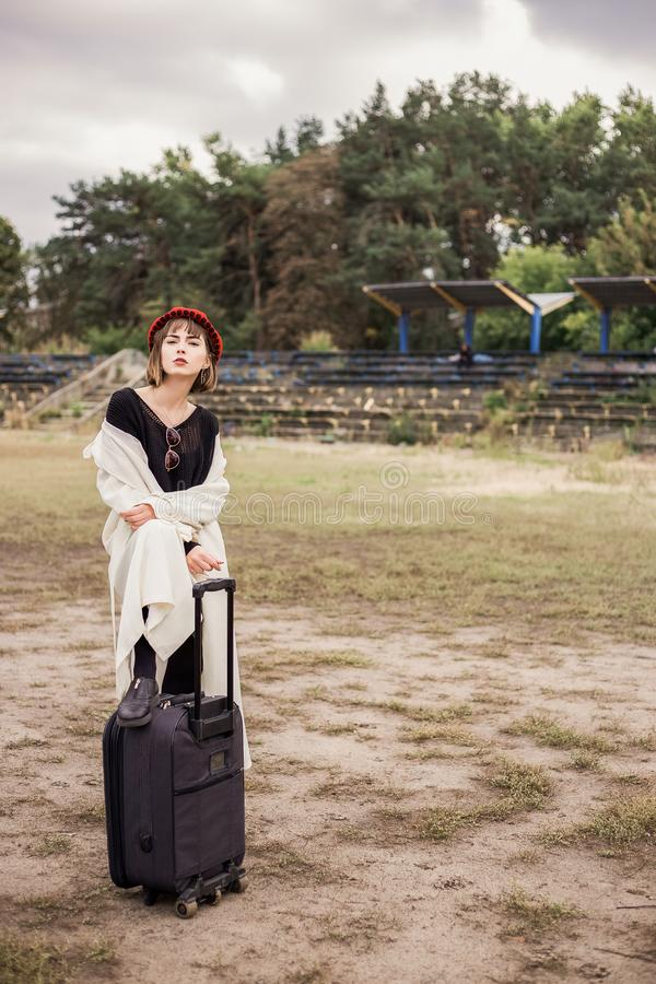 Stylish girl in light clothes, red hat, black suitcase. Cute girl in bright beret, bad weather stock image