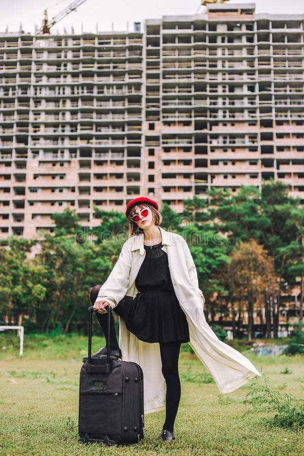 Stylish girl in light clothes, red hat, black suitcase. Cute girl in bright beret, bad weather royalty free stock images
