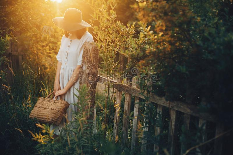 Stylish girl in linen dress holding rustic straw basket at wooden fence  in sunset light. Boho woman relaxing and posing in summer royalty free stock photo