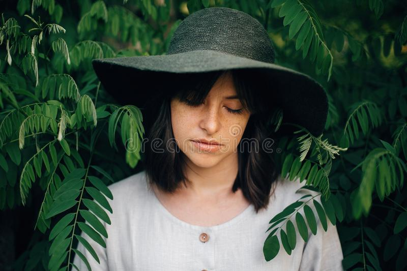 Stylish girl in linen dress posing at green branches. Portrait of calm boho woman in hat among acacia leaves in summer countryside stock photography
