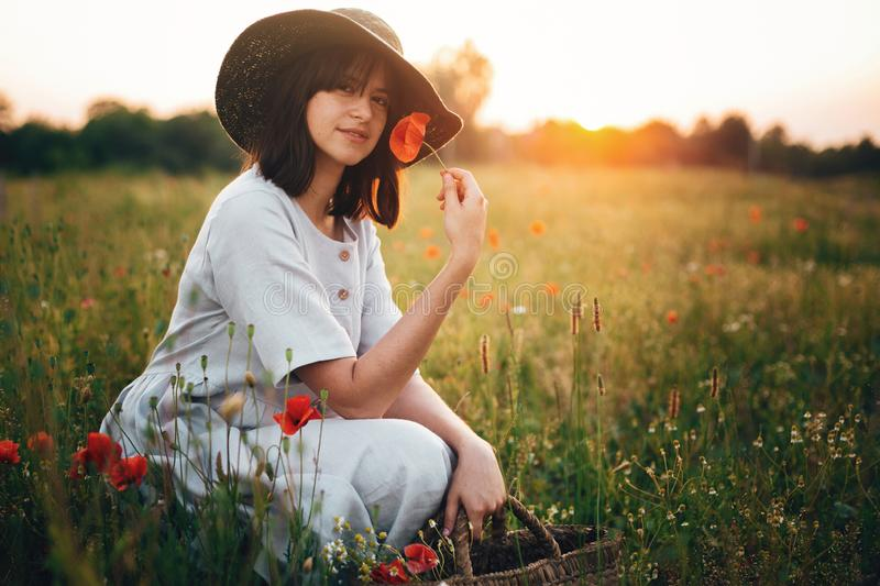 Stylish girl in linen dress smelling poppy flower in meadow in sunset light with flowers in rustic straw basket. Boho woman in hat royalty free stock photo