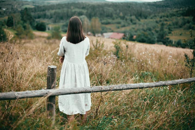 Stylish girl in linen dress standing at aged wooden fence among herbs and wildflowers, looking at field. Boho woman relaxing in stock photography