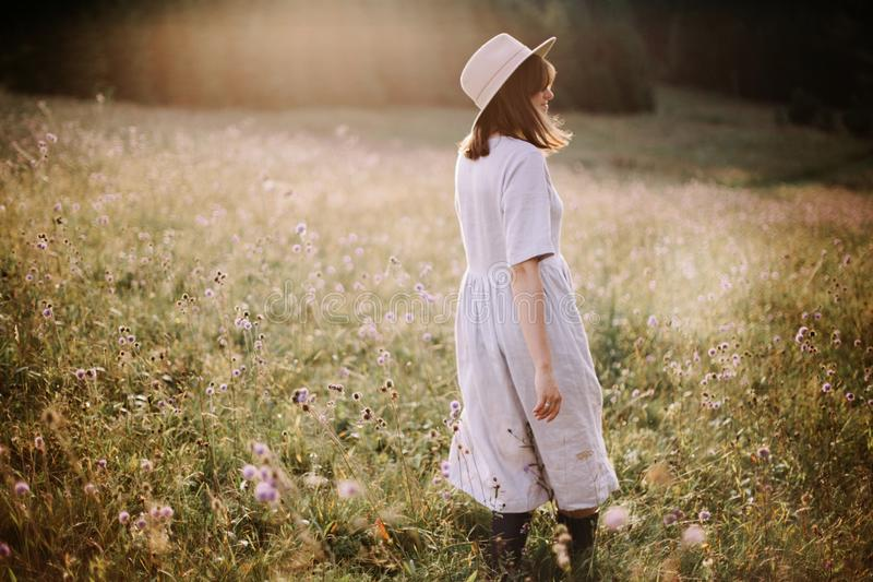 Stylish girl in linen dress walking among wildflowers in sunny meadow in mountains. Boho woman relaxing in countryside flowers at royalty free stock images