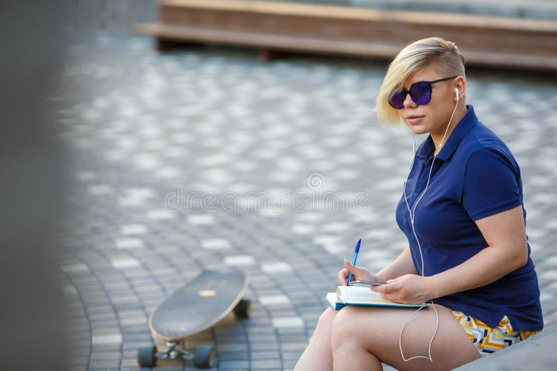 Stylish girl listens headphones writes in notebook stock images