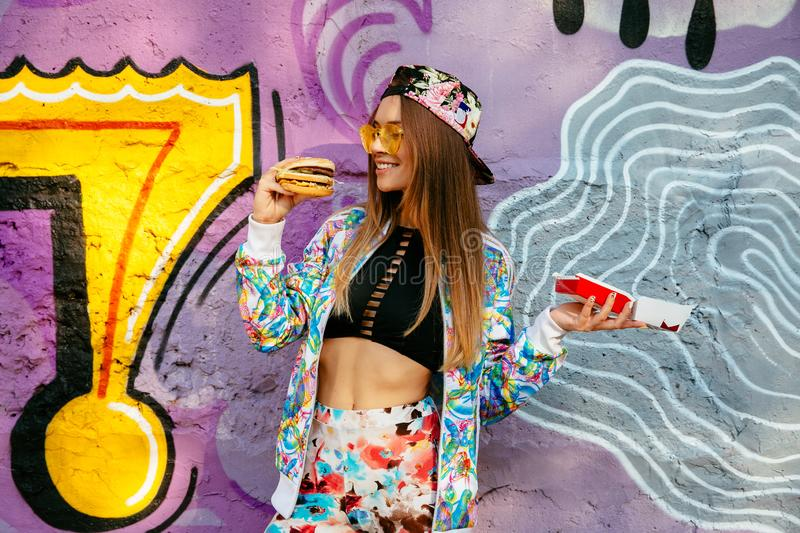 Stylish girl looking at hamburger, standing near the wall with graffiti. Smiling pretty girl ready to eat a hamburger. Dressed in bright clothes, fashion cap, in stock image