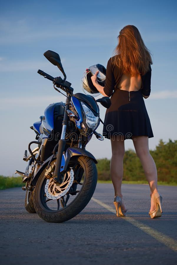 Stylish girl and motorcycle at sunset stock images
