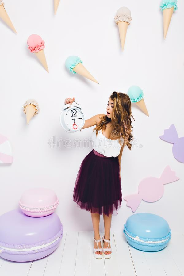 Stylish girl nervous because the guests are late for her birthday party. Attractive elegant young woman in violet skirt royalty free stock image