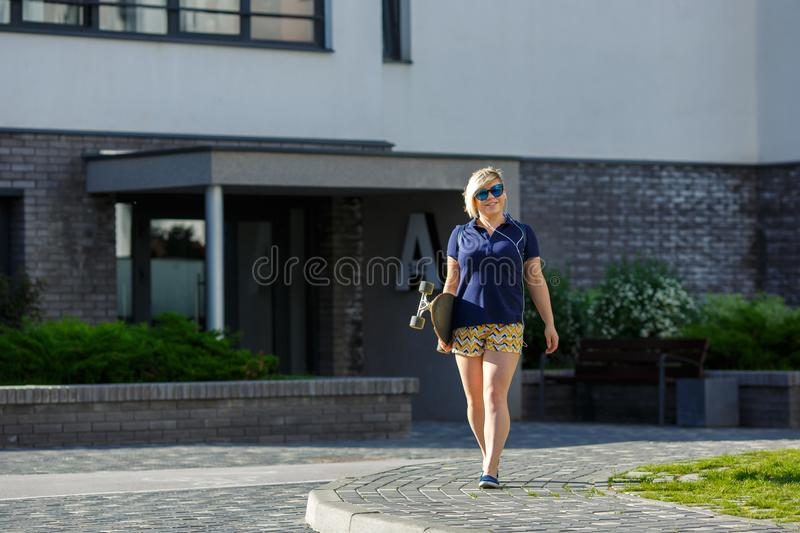Plus size girl with a longboard walking stock photo