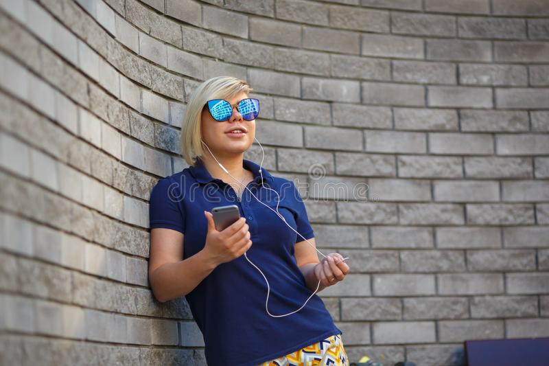 Stylish girl in sunglasses listens to headphones stock photography
