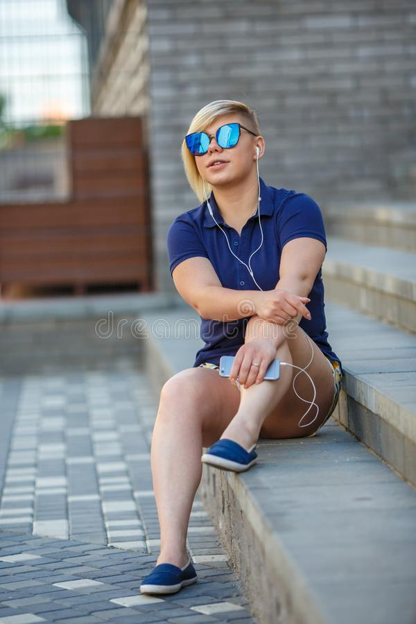 Stylish girl in sunglasses listens to headphones royalty free stock photos