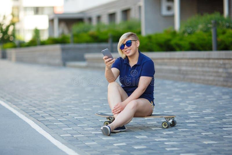 Stylish girl plus size sitting on a longboard stock image